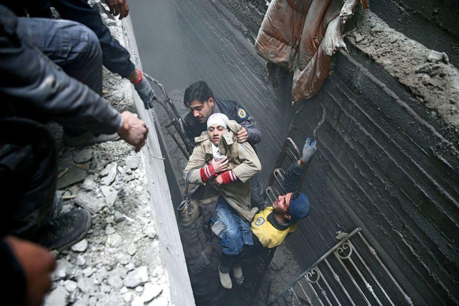 Une jeune femme extirpée d'une cave par la défense civile à Douma, dans la Ghouta orientale.