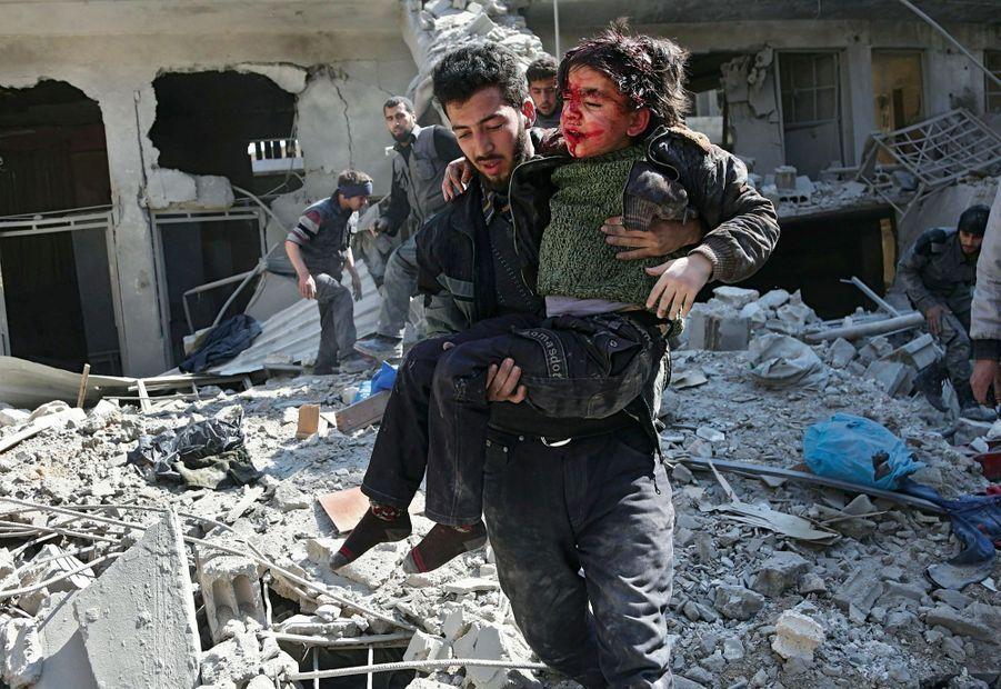 Le 21 février, un petit garçon blessé dans les bras d'un sauveteur après le bombardement aérien de Hamouria, dans la Ghouta orientale.