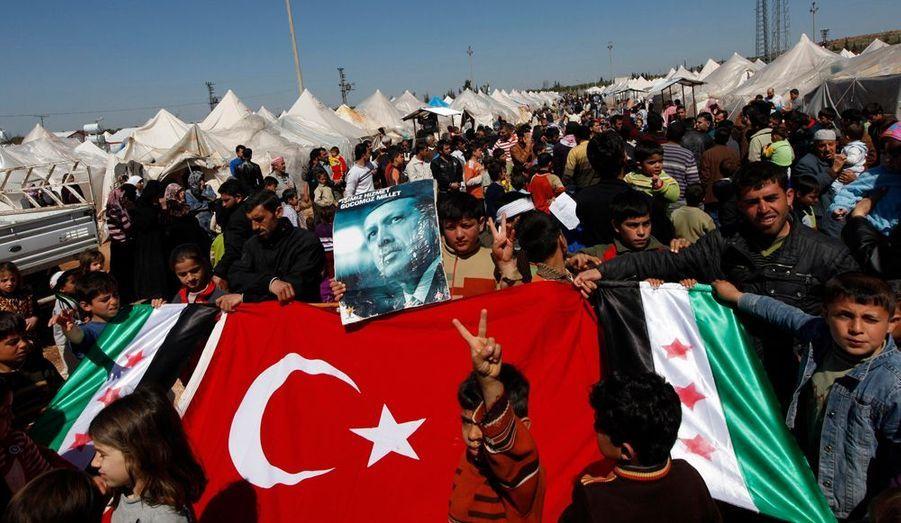 Les manifestants tiennent, en plus du drapeau syrien, le drapeau turc et une photo du Premier ministre, Recep Tayyip Erdogan.