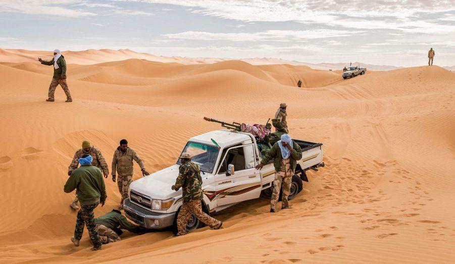 Des soldats de la brigade Tende sortent leur 4 x 4 du sable, entre l'erg de Mourzouk et l'Akakus. Dans les vallées de sable ceinturées par les massifs rocheux, autour des grands sites pétroliers du désert, les brigades patrouillent. Ici, les repères n'existent plus. La moindre forme qui surgit de l'horizon précipite le temps, et les 4 x 4 se lancent dans des poursuites effrénées. Le reste est attente.