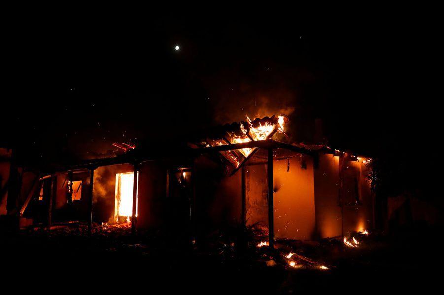 Une maison en flammes à Mati, près d'Athènes, lundi.