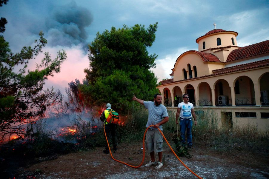 Des habitants tentent de combattre le feu à Rafina, près d'Athènes, lundi.