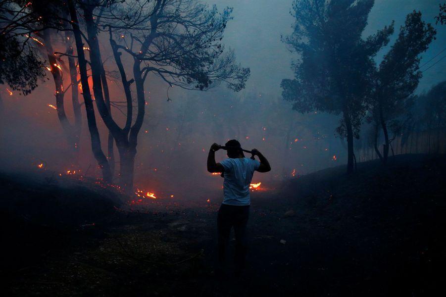 Un homme, protégé d'un simple chiffon, face à l'incendie à Rafina, près d'Athènes, lundi.
