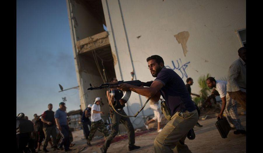 Depuis que les rebelles sont entrés dans la capitale libyenne lundi 22 août, les combats continuent et les pillages se multiplient. Le photographe Rémi Ochlik témoignage en images des derniers jours de cette bataille sanglante. Toutes photos: Rémi Ochlik.Alors que les rebelles ont déferlé par surprise sur la ville de Tripoli lundi, les combats ont été le plus intense, mardi 23 aout, lors de la prise du QG de Kadhafi Bab Al-Azazia. Tandis que le gros des troupes de Kadhafi recule vers la banlieue sud de la ville, de nombreux tireurs embusqués continuent de cribler de balles les rebelles comme celui-ci dans Bab Al-Azazia.