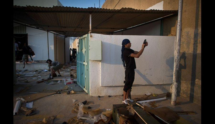 Certains rebelles commencent le pillage alors que les combats sont encore loin d'avoir cessé. Ce sont d'abord les immenses dépôts d'armes du dictateur qui les intéressent, puis n'importe quel colifichet qui leur tombe sous la main, et Bab Al-zazia en regorge.
