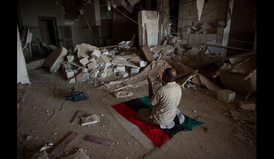 D'autres encore, comme ce caméraman du Conseil National de Transition Rebelle, prennent un instant pour rendre grâce à dieu de leur victoire. Agenouillé dans le hall de réception central de Bab Al-Azazia, il utilise son drapeau tricolore de la rébellion comme tapis de prière.