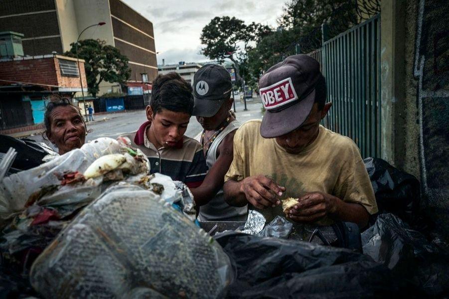 Affamés, des ados et une vieille dame se précipitent sur des restes de plateaux-repas. Dans le centre de Caracas, ils sont de plus en plus nombreux à avoir ce seul moyen de subsistance.