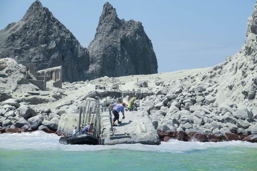 Des guides touristiques participent à l'évacuation des touristes pendant l'éruption de White Island, lundi.