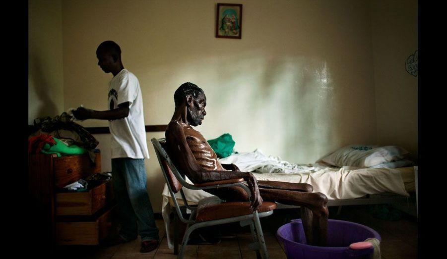 À 56 ans, Zacharia a passé ses derniers jours dans un établissement de soins palliatifs pour patients séropositifs tenu par l'église catholique à Harare. Il est mort trois heures seulement après avoir été photographié avec son neveu en train de lui donner un bain. Le Programme des Nations Unies pour le développement a dernièrement qualifié le Zimbabwe de pire pays au monde où vivre.
