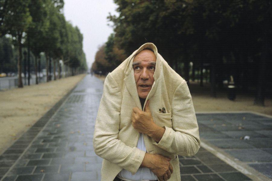 Michel Piccoli se protège de la pluie sur les Champs-Elysées. 27août 1991.