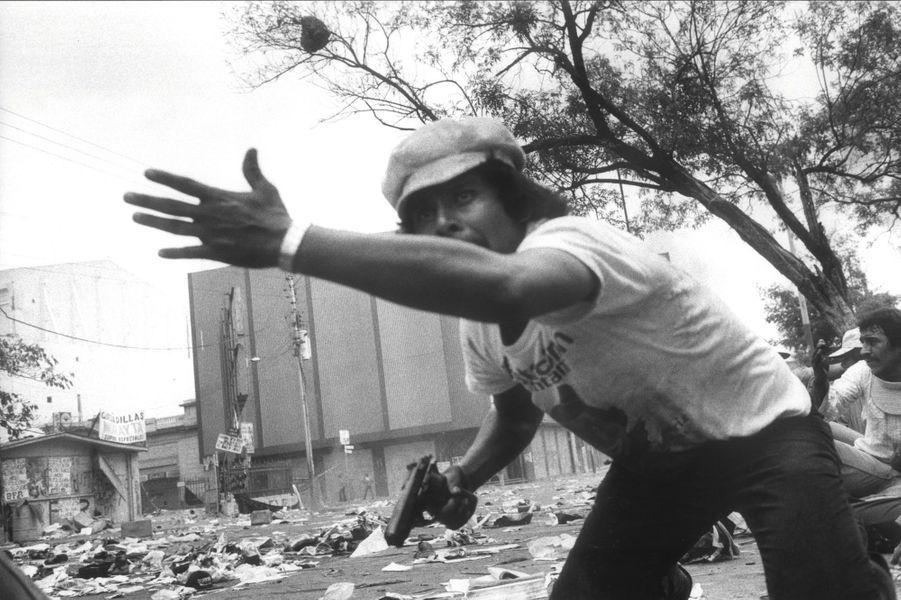 San Salvador (Salvador), mars1980. Pistolet au poing, un manifestant pendant les émeutes qui accompagnent les obsèques de MgrRomero, un prélat de gauche assassiné par les milices d'extrême droite.