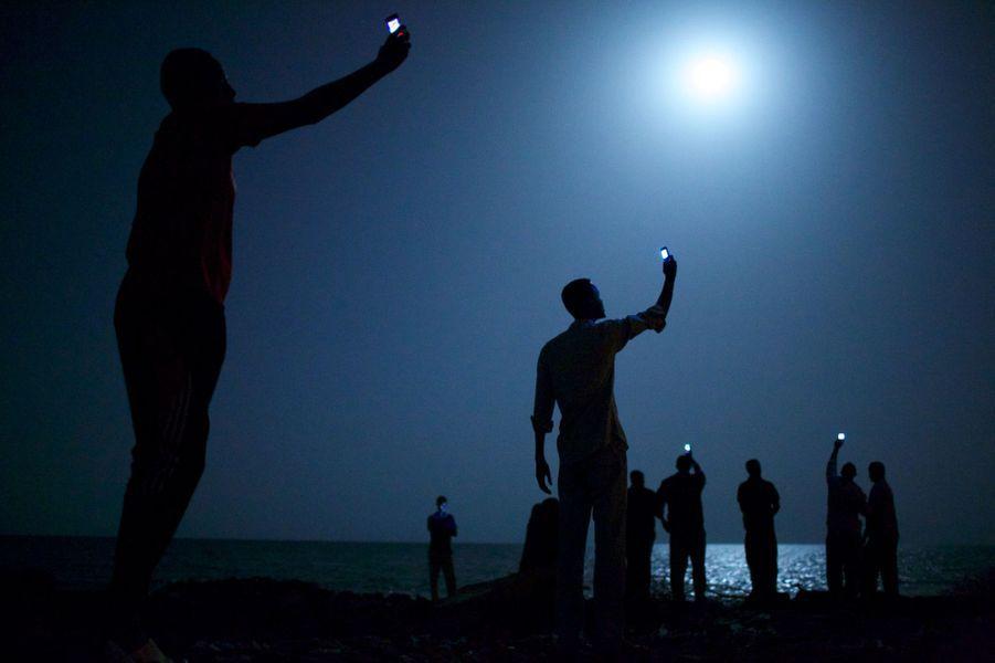 John Stanmeyer, USA, VII for National Geographic 26 février 2013, Djibouti City, DjiboutiLes migrants tentent de capter avec leurs téléphones portables un signal ténu de leurs proches restés en Somalie, leur pays d'origine de l'autre côté de la baie.