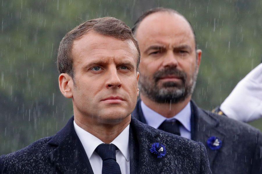 Emmanuel Macron et Edouard Philippe sous la pluie, devant la statue du Général De Gaulle, place Clémenceau, à Paris.