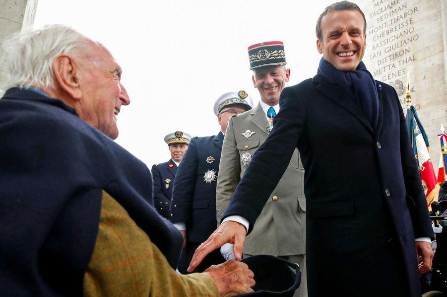 Emmanuel Macron salue Jacques Lewis, un ancien combattant, mercredi sous l'Arc de Triomphe.