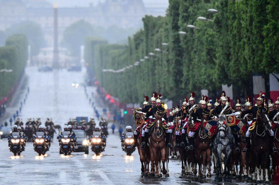La voiture d'Emmanuel Macron remonte les Champs-Elysées, mercredi.