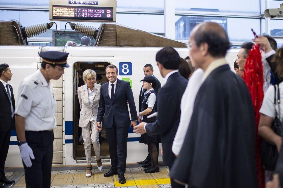 Emmanuel et Brigitte Macron arrivent à Kyoto et descendent du Shinkansen, un train à grande vitesse.