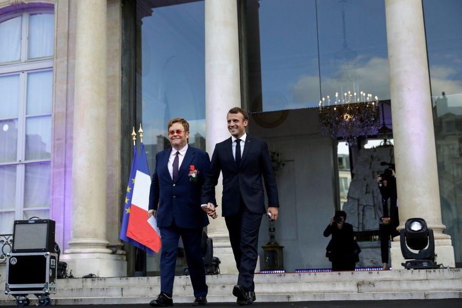 Elton John, tout juste décoré de la Légion d'honneur, et Emmanuel Macron arrivent main dans la main sur la scène.