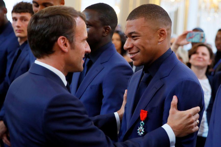 Le président décore Kylian Mbappé.