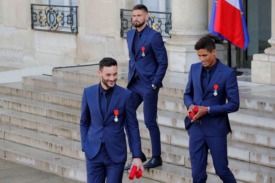 Giroud, Lloris, Varane quittent l'Elysée, légion d'honneur accrochée à la veste.