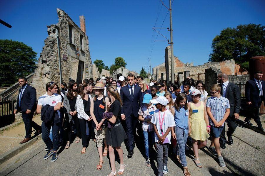 Le président de la République visite avec des enfants les ruines du village martyr.