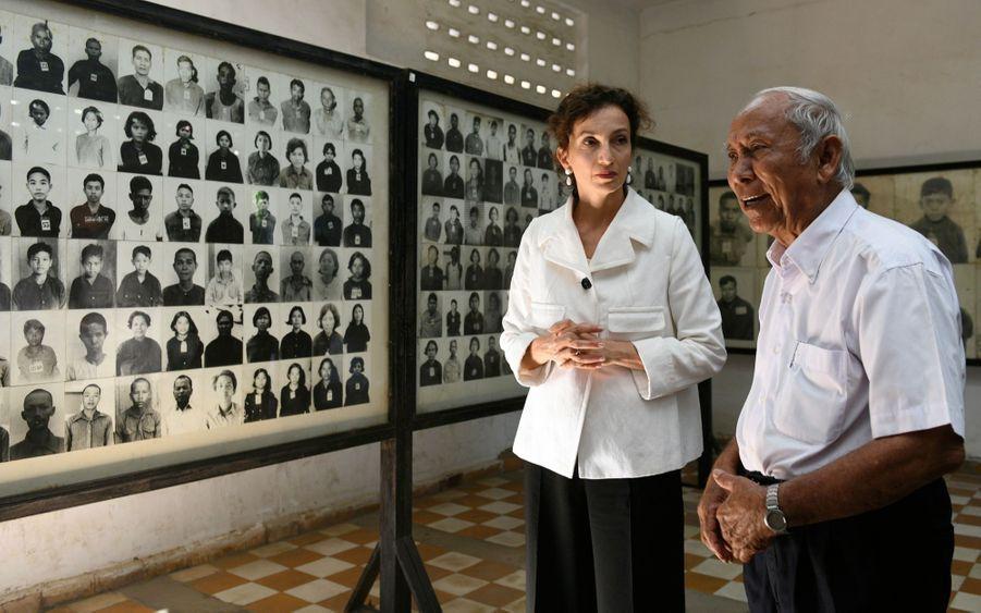 Au musée du Génocide de Tuol Sleng à Phnom Penh, la Directrice Générale de l'Unesco Audrey Azoulay écoute attentivement Mum Mey, un survivant et ex-prisonnier de la prison autrefois baptisée S-21, le 6 décembre 2018. Le musée du génocide Tuol Sleng traite du génocide cambodgien, commis entre 1975 et 1979 dans le Kampuchea démocratique des Khmers Rouges.