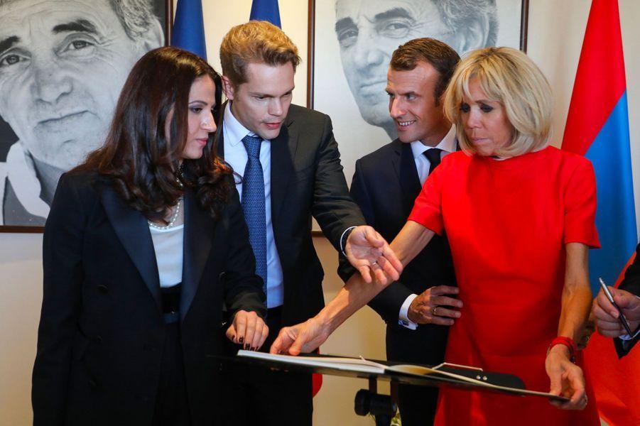 Emmanuel et Brigitte Macron signent le livre d'or. A leurs côtés, Nicolas Aznavour.