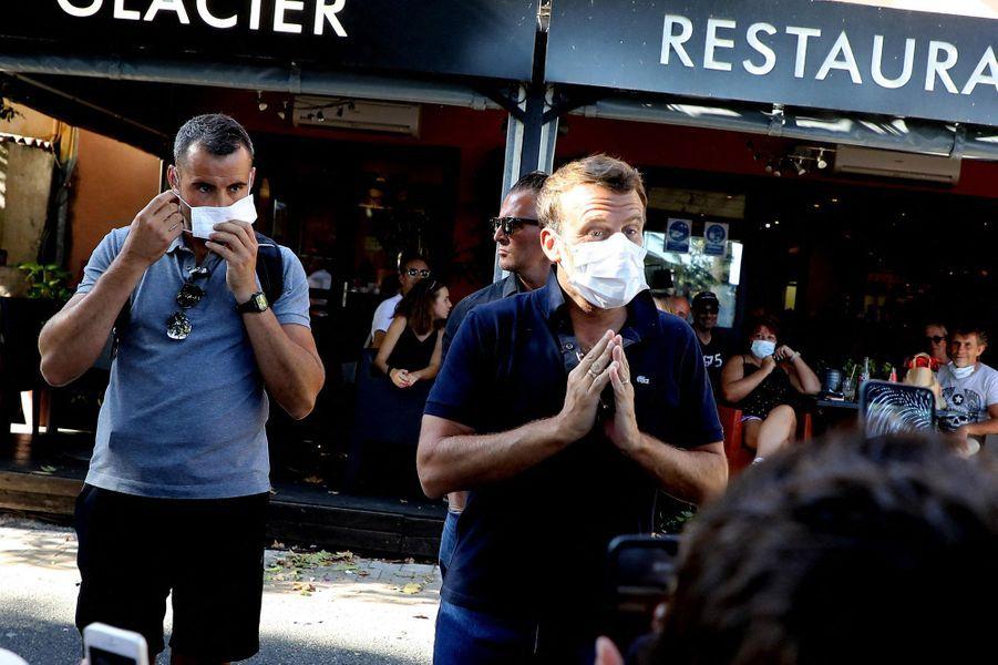 Emmanuel Macron, masqué, salue la foule.