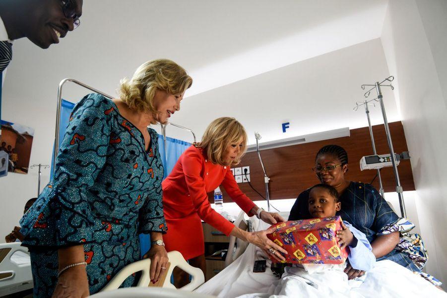 Brigitte Macron et Dominique Ouattara ont visité l'Hôpital Mère-Enfant de Bingerville, en banlieue d'Abidjan, où elles ont été accueillies par le personnel soignant, avant de distribuer des cadeaux de Noël aux jeunes patients.
