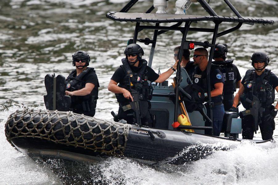La vedette transportant Brigitte Macron et Melania Trump est escortée par la police.