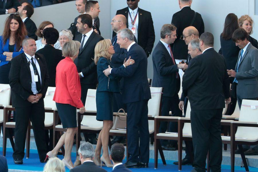 Brigitte Macron salue Bruno le Maire lors du défilé du 14 juillet sur les Champs-Elysées.