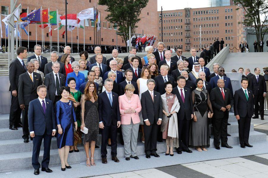 Les dirigeants du G20 et les conjoint(e)s posent pour une photo de famille entourant Angela Merkel etJoachim Sauer avant un concert à la nouvelle Philharmonie de l'Elbe.