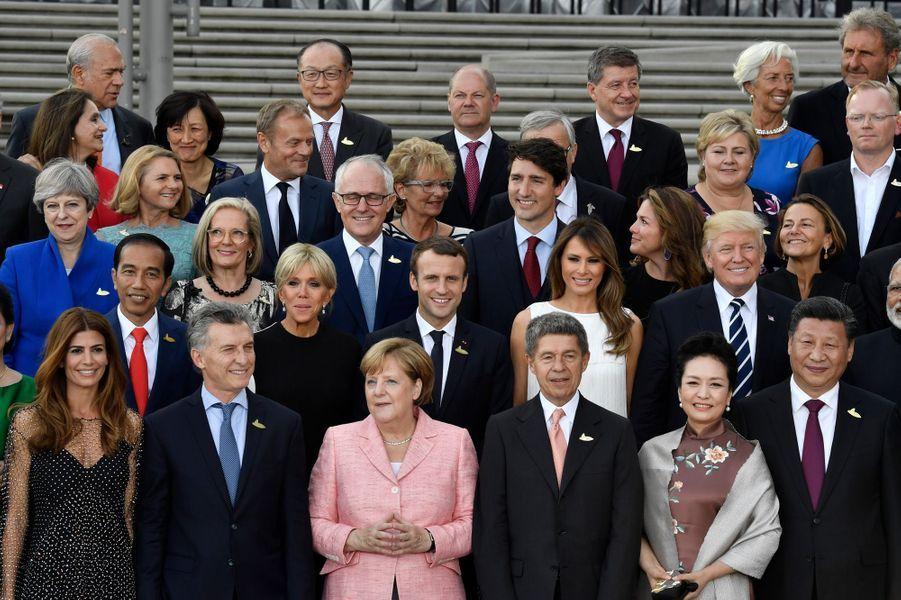 Les dirigeants du G20 et les conjoint(e)s posent pour une photo de famille entourant Angela Merkel etJoachim Saueravant un concert à la nouvelle Philharmonie de l'Elbe.