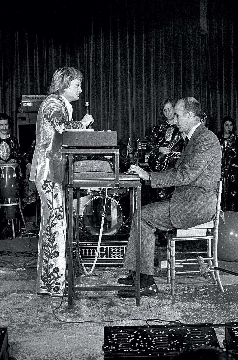Elysée, 17 décembre 1975.Assis sur des annuaires, Valéry Giscard d'Estaing joue du piano électrique pour Claude François. Il est le premier président à participer au spectacle de l'Arbre de Noël.