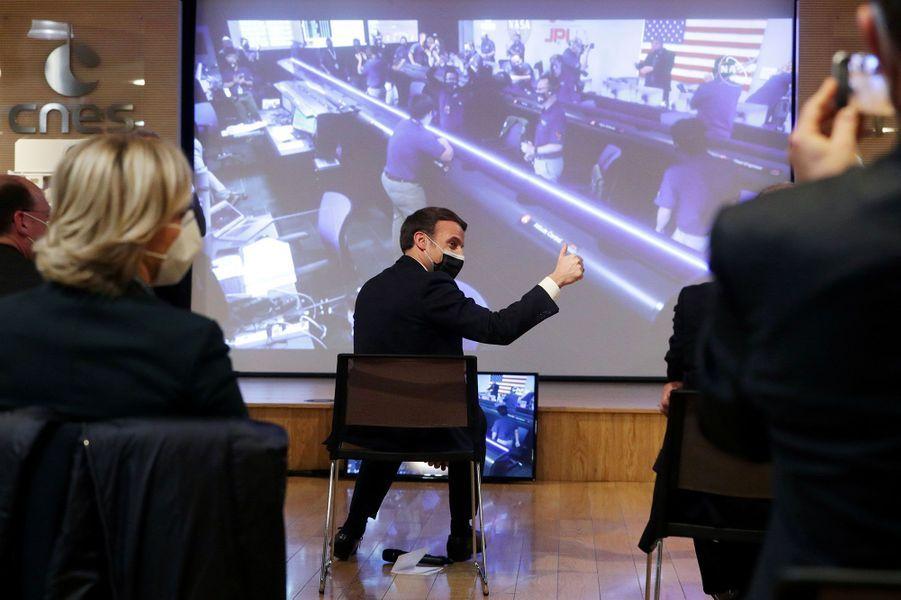 Emmanuel Macron, pouce levé, alors que l'écran de contrôle diffuse des images de la salle de contrôle du Jet Propulsion Laboratory, en Californie, où les ingénieurs américains exultent après le succès de la mission «Perseverance».