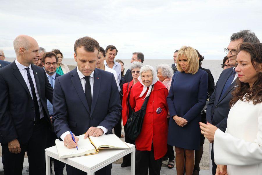 Au parc de la Mémoire, Emmanuel Macron laisse un mot dans le livre d'or.