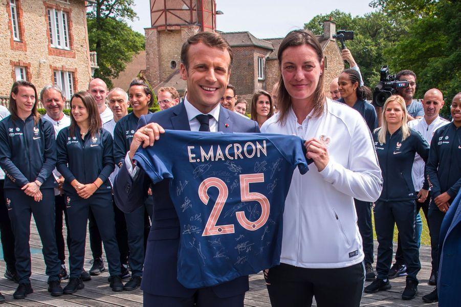 Emmanuel Macron avec Corinne Diacre. Le président a reçu un maillot à son nom.