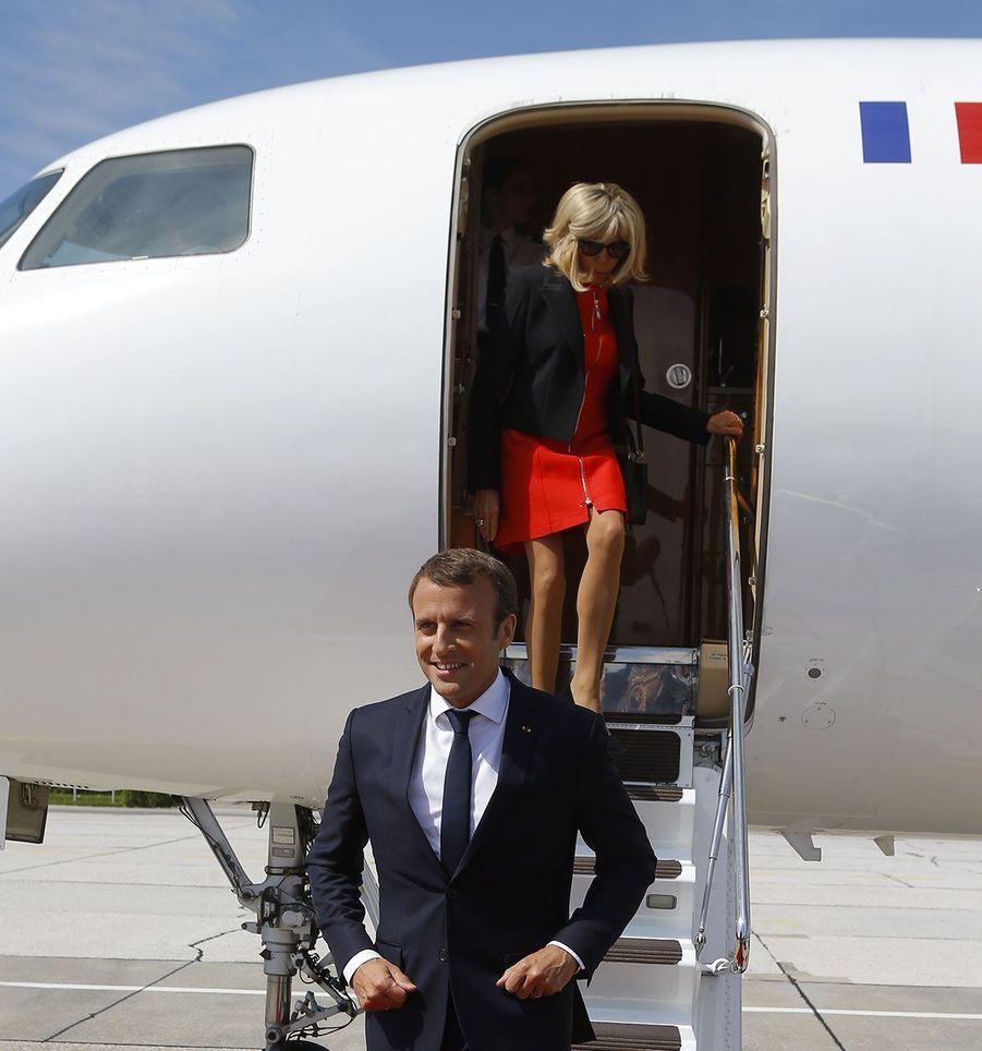 La première dame Brigitte Macron le suit à la descente de l'avion.