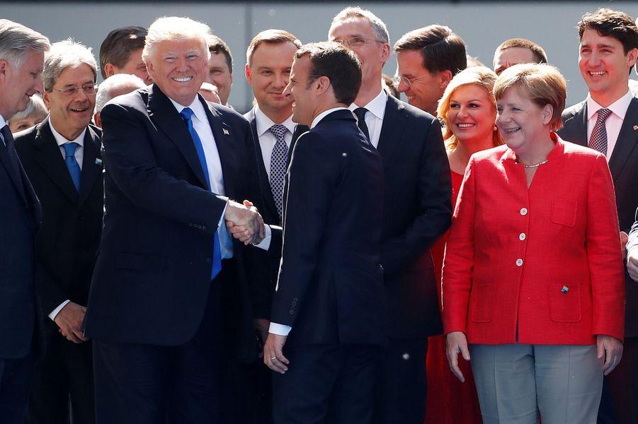 Au sommet de l'Otan, poignée de mains entre Donald Trump et Emmanuel Macron, sous le regard amusé d'Angela Merkel.