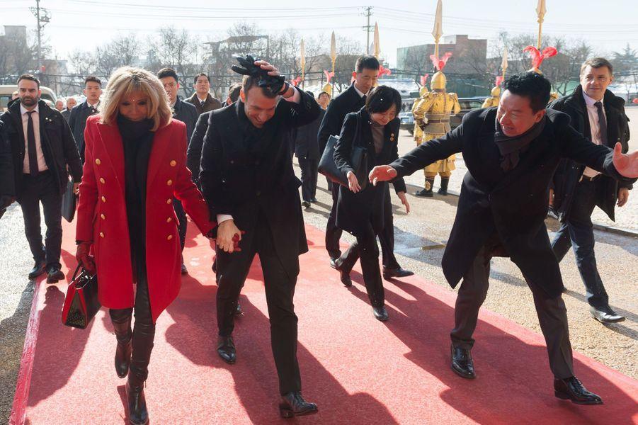 Emmanuel Macron, accompagné de son épouse, se protège des projections d'eau lors de son arrivée auPalaisDaminggong, à Xian.