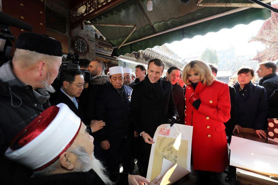 Emmanuel et Brigitte Macron reçoivent un cadeau lors d'une visite de la Grande Mosquée de Xian.