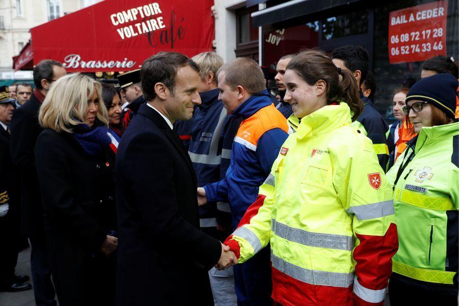 Emmanuel Macron et son épouse Brigitte saluent les secouristes devant Le Comptoir Voltaire.