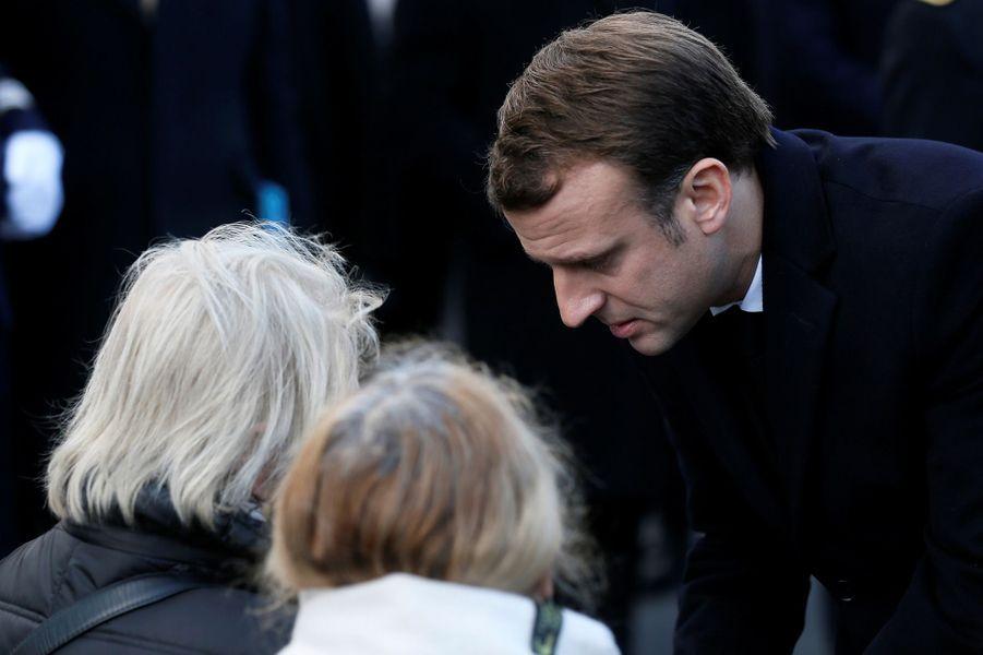 Emmanuel Macron saluant les familles des victimes lors de la cérémonie devant Le Carillon et Le Petit Cambodge.