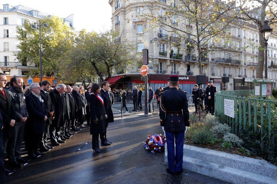 Emmanuel Macron et Anne Hidalgo lors de la minute de silence à La Bonne bière, rue de la Fontaine au Roi. La plaque est située sur lagrille du jardin, boulevard Jules Ferry