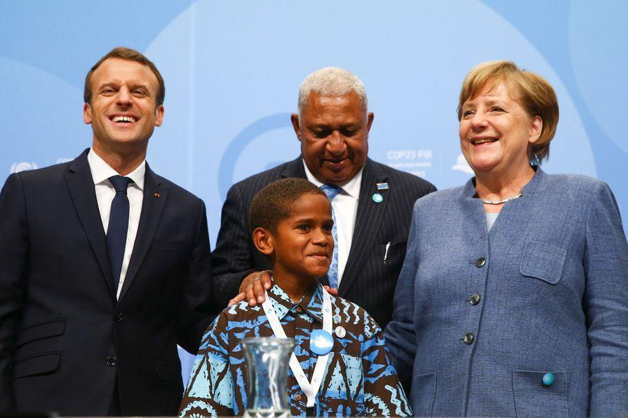 Emmanuel Macron, le Premier ministre fidjienFrank Bainimarama, la chancelière allemande Angela Merkel et le petit TimothyNaulusalaau World Convention Center de Bonn pour la COP23, en début d'après-midi le 15 novembre 2017.