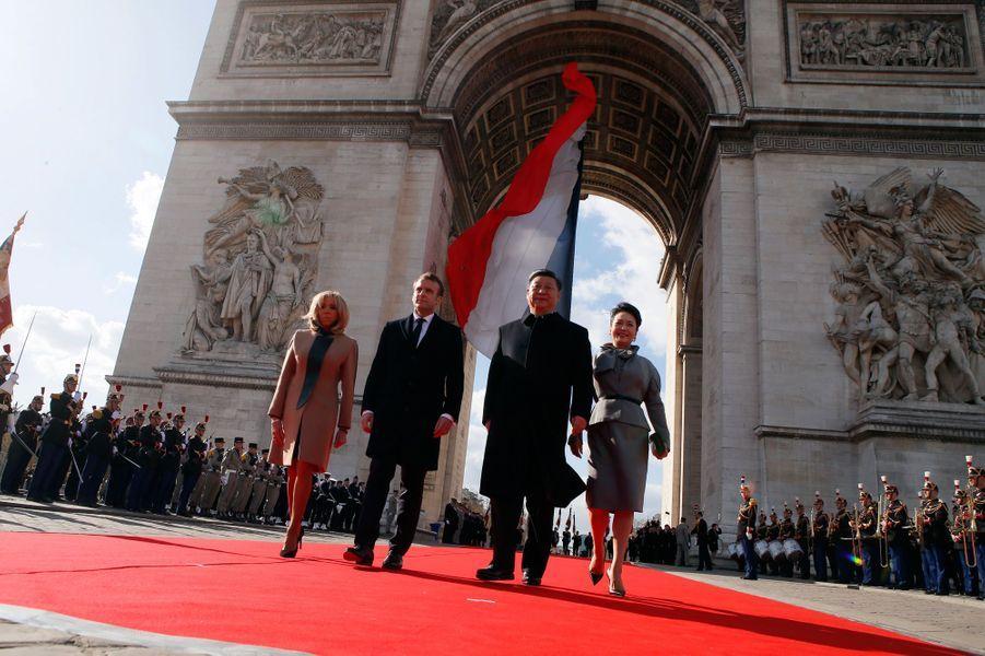 Emmanuel Macron et Xi Jinping, accompagnés de leurs épouses, lors de la cérémonie officielle à l'Arc de Triomphe.