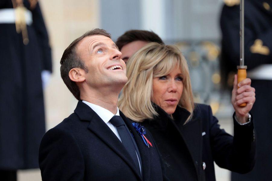 Emmanuel et Brigitte Macron sous les parapluies