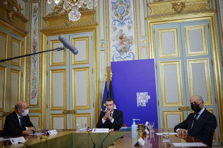 Emmanuel Macron lors d'une visioconférence le 12 décembre pour le Sommet des hautes ambitions climatiques. Il est entouré du ministre des Affaires étrangères Jean-Yves Le Drian et du président du Conseil constitutionnel, Laurent Fabius.