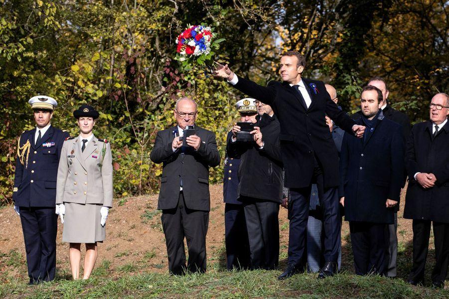 """Avant une minute de silence et la sonnerie aux morts, Emmanuel Macron lance un bouquet de fleurs dans un """"entonnoir"""", non loin du Point X."""