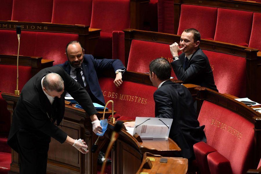 Désinfection des micros, le 7 avril, sous les yeux d'Edouard Philippe, Olivier Véran et Olivier Dussopt.