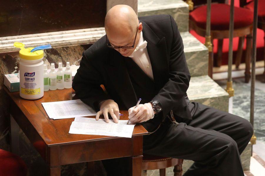 Un agent de l'Assemblée nationale, ganté, le 19 mars lors d'une session extraordinaire de questions au gouvernement.